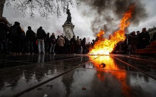 epa07214673 A trashcan burns on Place de la Republique as students demonstrate against the increase of the subscription fees for foreigners students, in Paris, France, 07 December 2018. This movement takes place while the government is facing a major contestation by the so called movement of the Gilets Jaunes (Yellow Vests).  EPA/IAN LANGSDON
