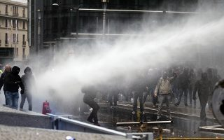 Protestors are held back by a police water cannon during an anti-migrant demonstration outside of EU headquarters in Brussels, Sunday, Dec. 16, 2018. (AP Photo)