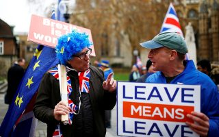 FILE PHOTO: A Brexit supporter holds a placard next to anti-Brexit demonstrator during a protest opposite the Houses of Parliament, London, Britain, December 4, 2018. REUTERS/Henry Nicholls/File Photo