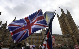 Anti-Brexit campaigners wave flags in front of parliament in London, Wednesday, Dec. 5, 2018. Britain's Brexit debate has become a bruising battle between lawmakers and Prime Minister Theresa May's government. May is trying to keep her EU divorce deal on track Wednesday after her government was dealt a double blow by Parliament. (AP Photo/Kirsty Wigglesworth)
