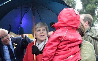 Η Τερέζα Μέι μιλάει σε μητέρα που κρατάει αγκαλιά το παιδί της. Η Βρετανίδα πρωθυπουργός «όργωσε» τη χώρα για να πείσει υπέρ του σχεδίου της, το κλίμα όμως παραμένει πολύ βαρύ γι' αυτήν.