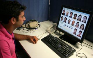 Αξιωματικός  της ΕΛΑΣ ελέγχει στα μόνιτορ της Υπηρεσίας Διαβατηρίων τις φωτογραφίες ελλήνων πολιτών που έχουν υποβάλλει αίτηση για διαβατήριο  , Αθήνα Τρίτη  29 Αυγούστου 2006.