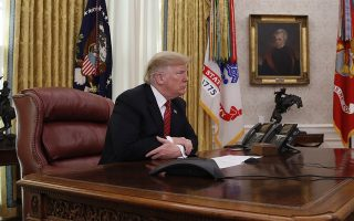 President Donald Trump pauses while speaking to members of the five branches of the military by video conference on Christmas Day, Tuesday, Dec. 25, 2018, in the Oval Office of the White House. The military members were stationed in Guam, Qatar, Alaska, and two groups in Bahrain. (AP Photo/Jacquelyn Martin)