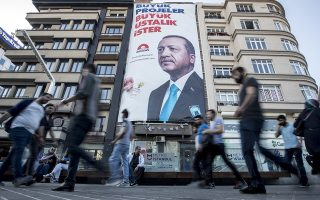 epa06794251 People walks in front of a huge picture of Turkish President Recep Tayyip Erdogan in Istanbul, Turkey, 08 June 2018. Turkish President Erdogan announced on 18 April 2018 that Turkey will hold snap elections on 24 June 2018. The presidential and parliamentary elections were scheduled to be held in November 2019, but government has decided to change the date following the recommendation of the Nationalist Movement Party (MHP) leader Devlet Bahceli.  EPA/SEDAT SUNA