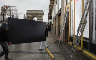 Workers carry a wooden piece to protect shop windows on the Champs-Elysees avenue, Friday, Dec. 7, 2018 in Paris. Many shop owners across the French capital are getting ready for the violence, setting up walls with carton boards to protect their windows. The Arc de Triomphe is seen in background. (AP Photo/Francois Mori)