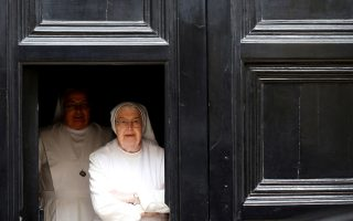 Nuns look out from behind a door as Pierbattista Pizzaballa, the acting Latin Patriarch of Jerusalem, makes to his way to the West Bank town of Bethlehem from the Patriarchate in Jerusalem's Old City December 24, 2018. REUTERS/Ronen Zvulun     TPX IMAGES OF THE DAY