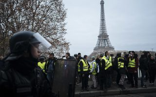 Demonstrators wearing yellow vests are blocked by riot police officers on the Bir Hakeim Bridge as the Eiffel Tower is seen in background in Paris, Saturday, Dec. 29, 2018.  Yellow vest protesters marched on the headquarters of leading French broadcasters Saturday, as small groups turned out around France despite waning momentum for their movement.  Police arrested some protesters near the Eiffel Tower, but by nightfall calm returned to the area. (AP Photo/Kamil Zihnioglu)