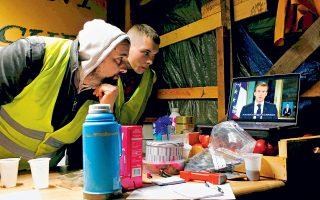 Ακτιβιστές παρακολουθούν το τηλεοπτικό διάγγελμα Μακρόν στα περίχωρα της Νάντης.