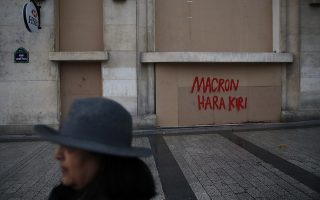 A woman walks past a bank protected with wooden planks, in Paris, Sunday, Dec. 9, 2018. Paris monuments reopened, cleanup workers cleared debris and shop owners tried to put the city on its feet again Sunday, after running battles between yellow-vested protesters and riot police left 71 injured and caused widespread damage to the French capital. (AP Photo/Christophe Ena)