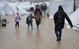 Γυναίκα με τα παιδία της περπατούν κατά τη διάρκεια έντονης χιονόπτωσης στο hot spot προσφύγων και μεταναστών της Μόριας στη Λέσβο, τη Δευτέρα 9 Ιανουαρίου 2017. Σφοδρή χιονοθύελλα πλήττει όλα τα νησιά του βορείου Αιγαίου, που εντάθηκε τις πρώτες μεταμεσημβρινές ώρες δημιουργώντας τεράστια προβλήματα. Το σύνολο του οδικού δικτύου της Λέσβου είναι κλειστό, ενώ τα μηχανήματα του δήμου και της περιφέρειας βορείου Αιγαίου καθαρίζουν τους δρόμους, που όμως πολύ σύντομα κλείνουν ξανά. Πολλά είναι και τα αποκλεισμένα χωριά. Ιδιαίτερα προβλήματα αντιμετωπίζουν τα χωριά της δυτικής Λέσβου που σε κάποια σημεία το χιόνι έφτασε το ένα μέτρο, αλλά και χωριά της βόρειας Λέσβου. Χιόνι στρώθηκε ακόμα και στο κέντρο της πόλης της Μυτιλήνης μέχρι τη θάλασσα.   . ΑΠΕ- ΜΠΕ/ ΑΠΕ-ΜΠΕ /ΣΤΡΑΤΗΣ ΜΠΑΛΑΣΚΑΣ