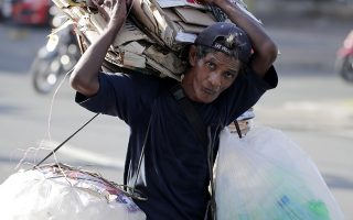 epa07221094 A Filipino carries recyclable materials at a street in Manila, Philippines, 10 December 2018. Human Rights Day is observed every year on 10 December, which is the anniversary of the day that the United Nations General Assembly adopted, in 1948, the Universal Declaration of Human Rights. In 2018, Human Rights Day will mark the 70th anniversary of the Universal Declaration of Human Rights. This year's UN Human Rights Day observations will focus on highlighting the proclamations outlined in the UDHR, specifically Article One of the Declaration which states that 'All human beings are born free and equal in dignity and rights'.  EPA/FRANCIS R. MALASIG