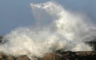 Wind driven waves crash onto the breakwater at the mouth of the Cuyahoga River where the lighthouse watches over the harbor, Wednesday, March 15, 2006, in Cleveland. (AP Photo/The Plain Dealer, Thomas Ondrey) ** MANDATORY CREDIT  **