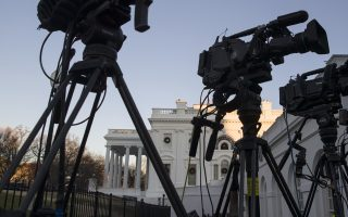 The setting sun illuminates the White House as video cameras stand ready during a partial federal shutdown, Saturday, Dec. 22, 2018, in Washington. The partial federal shutdown was expected to drag into Christmas as President Donald Trump and congressional leaders remained stuck in a standoff over his border wall with Mexico. (AP Photo/Alex Brandon)