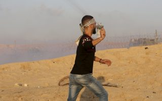 A protester hurls stones at Israeli troops near the fence of the Gaza Strip border with Israel during a protest on the beach near Beit Lahiya, northern Gaza Strip, Monday, Nov. 19, 2018. (AP Photo/Adel Hana)