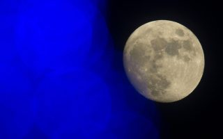 The moon is seen near a Christmas lights in Beijing Sunday, Dec. 15, 2013. China's first moon rover touched the lunar surface and left deep traces on its loose soil, state media reported Sunday, several hours after the country successfully carried out the world's first soft landing of a space probe on the moon in nearly four decades. (AP Photo/Ng Han Guan)