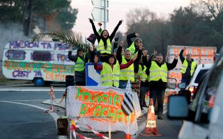 Protesters wearing yellow vests, the symbol of a French drivers' protest against higher diesel fuel prices, occupy a roundabout in Cissac-Medoc, France, December 5, 2018.  The slogan reads