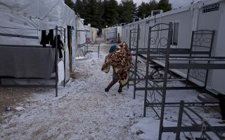 A Syrian refugee woman hangs a wet blanket to dry outside her shelter at the refugee camp of Ritsona about 86 kilometers (53 miles) north of Athens, Monday, Jan. 9, 2017. Over 62,000 refugees and migrants are stranded in Greece after a series of Balkan border closures and an European Union deal with Turkey to stop migrant flows. (AP Photo/Muhammed Muheisen)