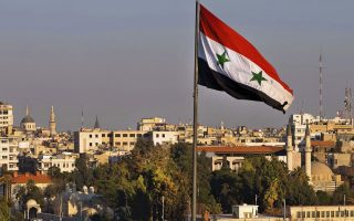 FILE - In this Feb. 28, 2016 file photo a Syrian national flag waves as vehicles move slowly on a bridge during rush hour, in Damascus, Syria. A new Syrian law empowering the government to confiscate property is threatening to leave refugees stuck in Europe with no homes to return to. (AP Photo/Hassan Ammar, file)