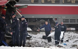 epa07243179 Police officers remove the body of a victim at the scene of crash between a bus and a train at a railway crossing in the village of Donje Medjurovo, some 10km from the city of Nis, Serbia, 21 December 2018. According to reports, the train slammed into a bus, which transported passengers from Donje Medjurovo to Nis, at a railway crossing that did not reportedly have a level crossing. Five people were killed and over 20 were injured, media added.  EPA/DJORDJE SAVIC