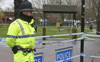 A police officer at a cordon near the Maltings in Salisbury, England,  Friday March 30, 2018, near to where Russian former double agent spy Sergei Skripal and his daughter Yulia were found on a bench after they were attacked with a nerve agent. The former Russian spy and his daughter who were victims of a nerve agent attack first came into contact with the deadly chemical at his home, police said as investigations continue. (Jonathan Brady/PA via AP)