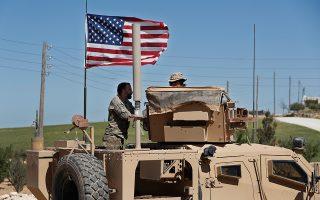 Μαχητής του Συριακού Στρατιωτικού Συμβουλίου του Μανμπίτζ συνομιλεί με Αμερικανό στρατιώτη σε φυλάκιο της υπό κουρδικό έλεγχο πόλης.