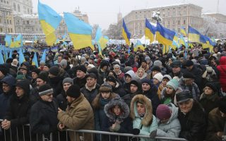 People with Ukrainian national flags gathered to support independent Ukrainian church near the St. Sophia Cathedral in Kiev, Ukraine, Saturday, Dec. 15, 2018. Ukraine's Orthodox clerics gather for a meeting Saturday that is expected to form a new, independent Ukrainian church, and Ukrainian authorities have ramped up pressure on priests to support the move. (AP Photo/Efrem Lukatsky)