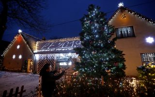 Vaclav Trunec, 46, adjusts the Christmas lighting decoration outside his house in the village of Chotovice near the town of Litomysl, Czech Republic, December 18, 2018. Picture taken December 18, 2018.   REUTERS/David W Cerny