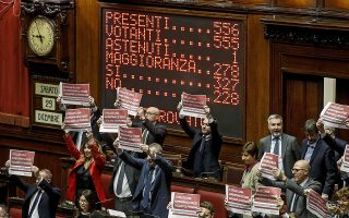 epa07253449 The electronic scoreboard and the protest of Democratic Party's deputies at the end of the vote of confidence on the budget law in the Chambre of Deputies in Rome, Italy, 29 December 2018. Chamber President Fico suspended the session for five minutes after Forza Italia deputies wore blue bibs with inscriptions such as 'Down the Hands of No Profit' and 'No Taxes'.  EPA/FABIO FRUSTACI
