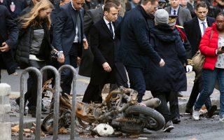 Ο Εμανουέλ Μακρόν, συνοδευόμενος από άνδρες της προσωπικής του ασφάλειας, επιθεωρεί σημείο του Παρισιού, όπου την προηγούμενη μέρα εκτυλίχθηκαν σοβαρές συγκρούσεις μεταξύ «Κίτρινων Γιλέκων» και αστυνομίας.