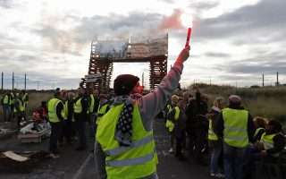 epa07205948 People wearing yellow vests block access to the oil refinery of Frontignan, southern France, 03 December 2018. The so-called gilets jaunes (yellow vests), a protest movement, which reportedly has no political affiliation, is protesting across the nation over high fuel prices.  EPA/GUILLAUME HORCAJUELO
