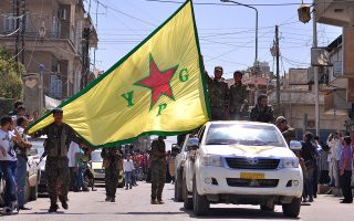 TOPSHOTSKurdish People's Protection Units (YPG) fighters wave their movement's flag as they parade in the northeastern Syrian town of Qamishli after returning from battling Islamic State (IS) group jihadists in Tal Abyad on the border with Turkey on June 24, 2015. Fighters from the YPG and Syrian rebel forces declared full control over Tal Abyad on June 23, less than a week after they began an advance on the jihadist-held town. AFP PHOTO / DELIL SOULEIMAN