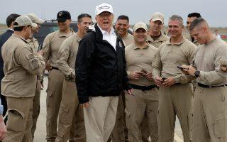 O Αμερικανός πρόεδρος Ντόναλντ Τραμπ ανάμεσα σε χαμογελαστούς συνοριοφύλακες.