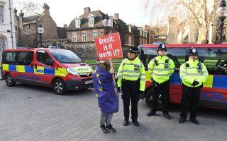 Ενας διαδηλωτής κατά του Brexit συζητάει με την αστυνομική φρουρά έξω από το Κοινοβούλιο στο Λονδίνο.