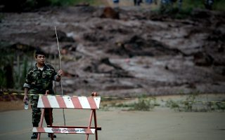epa07322973 A Brazilian soldier stand guards after the disaster caused by the breakage of a dam containing mineral waste from Vale, in Brumadinho, municipality of Minas Gerais, Brazil, 26 January 2019. At least 34 people have died and 300 are missing after the breakdown of the mining giant Vale's dam in Brazil, firefighters said this Saturday. One of Vale's dams, in an iron mine in the jurisdiction of Brumadinho, municipality of Minas Gerais (southeast), broke down this Friday and a river with mineral residues and mud buried the company's facilities and various homes in rural areas.  EPA/Antonio Lacerda