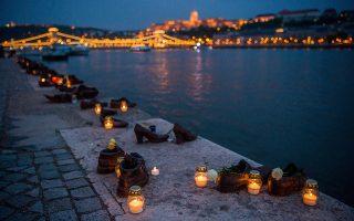 Δεκάδες κεριά φωτίζουν το μνημείο του Ολοκαυτώματος στην ανατολική όχθη του Δούναβη, στη Βουδάπεστη, κατά τον εορτασμό της Ημέρας Μνήμης για τα θύματα του Ολοκαυτώματος στην Ουγγαρία, στις 16 Απριλίου 2018. Αποτελούμενο από εξήντα σιδερένια ζευγάρια παπουτσιών, το μνημείο είναι αφιερωμένο στα θύματα της τρομοκρατίας των ντόπιων ναζιστών την περίοδο 1944-45, τα περισσότερα εκ των οποίων δολοφονήθηκαν στις όχθες του ποταμού και στη συνέχεια πετάχθηκαν στον βυθό του, αφού πρώτα είχαν αναγκαστεί να βγάλουν τα παπούτσια τους. (Zoltan Balogh/MTI via AP)