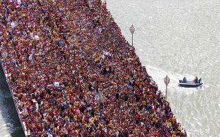 Λατρεία. Χιλιάδες ξυπόλητοι Φιλιππινέζοι ακολουθούν την πορεία πάνω από την γέφυρα και υπό την προστασία λιμενικών. Κάθε χρόνο τους τελευταίους αιώνες οι καθολικοί της χώρας ακολουθούν την λιτανεία του Μαύρου Ναζωραίου  που κρατά μέχρι το ξημέρωμα της επόμενης ημέρας. (AP Photo/Bullit Marquez)