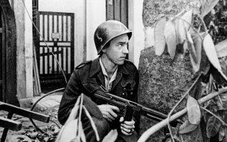 Κρατώντας ένα αυτόματο τυφεκιο σφιχτά στα χέρια του, ένας Γάλλος στρατιώτης προσπαθεί να προστατευτεί από τα πυρά ελεύθερων σκοπευτών στο Ανόι, καθώς έχουν κλιμακωθεί οι εχθροπραξίες μεταξύ των γαλλικών αποκιακών δυνάμεων και των κομμουνιστών ανταρτών Βιετμίνχ, κατά τη διάρκεια του Πρώτου Πολέμου της Ινδοκίνας, το 1947. (AP Photo)