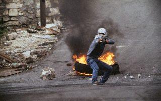 Με όπλο μία αυτοσχέδια ξύλινη σφεντόνα και βόλους για πυρομαχικά, αυτός ο νεαρός Παλαιστίνιος στέκεται πρόσωπο με πρόσωπο με τους Ισραηλινούς στρατιώτες κατά τη διάρκεια οδομαχιών στην πόλη της Ναμπλούς, στην κατεχόμενη Δυτική Όχθη, το 1988. ( AP Photo/Max Nash)