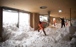 epaselect epa07275741 Emergency service workers clear snow from the inside of the Hotel Saentis on the Schwaegalp, Switzerland, after an avalanche came down, in Hundwil, Switzerland, 11 January 2019. According to local police, an avalanche has hit the the hotel 'Saentis' on 10 January afternoon, burrying cars and part of the restaurant. Several people were injured, the report stated.  EPA/GIAN EHRENZELLER
