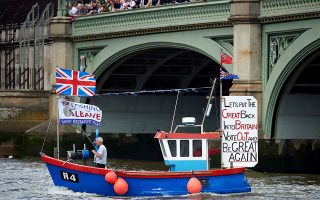 A boat decorated with flags and banners from the 'Fishing for Leave' group campaigning for a 'leave' vote in the EU referendum sail under Westminster Bridge toward the British Houses of Parliament as part of a