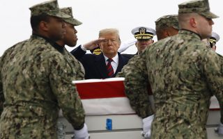 President Donald Trump salutes as a U.S. Navy carry team moves a transfer case containing the remains of Scott A. Wirtz, Saturday, Jan. 19, 2019, at Dover Air Force Base, Del. According to the Department of Defense, Wirtz, a civilian and former Navy SEAL from St. Louis, Mo., was killed Jan. 16, 2019, in a suicide bomb attack in Manbij, Syria. (AP Photo/Patrick Semansky)