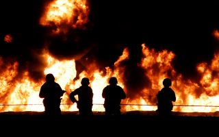 epa07298869 Soldiers stand guard in front of a wall of fire after an explosion of an illegal tap on Mexican oil company Pemex's pipeline in Tlahuilipan, state of Hidalgo, Mexico, late night 18 January 2019. At least 21 people died and 71 other people were wounded in the blast, according to official sources.  EPA/OASA
