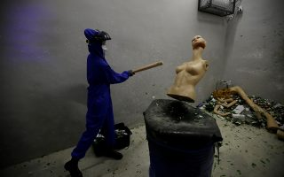A female customer wearing protective gear smashes a mannequin in an anger room in Beijing, China January 12, 2019. Picture taken January 12, 2019. REUTERS/Jason Lee