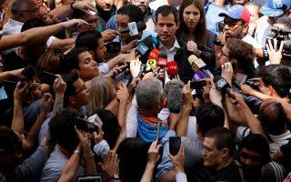 Συνοδευόμενος από τη σύζυγό του, ο Χουάν Γκουαϊδό συνομιλεί με δημοσιογράφους έξω από εκκλησία του Καράκας.