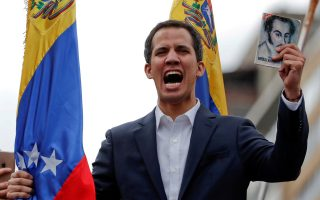 FILE PHOTO: Juan Guaido, President of Venezuela's National Assembly, holds a copy of Venezuelan constitution during a rally against Venezuelan President Nicolas Maduro's government and to commemorate the 61st anniversary of the end of the dictatorship of Marcos Perez Jimenez in Caracas, Venezuela January 23, 2019. REUTERS/Carlos Garcia Rawlins/File Photo