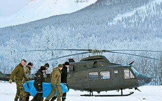 Αστυνομικοί και μέλη του Ερυθρού Σταυρού μεταφέρουν τη σορό ενός από τους τέσσερις σκιέρ που σκοτώθηκαν από χιονοστιβάδα.