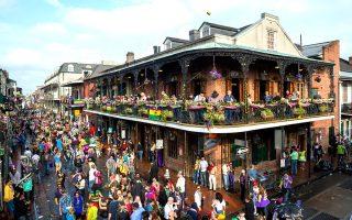 H ατμόσφαιρα της Mardi Gras: χρώματα, λάβαρα, καρναβαλιστές κάθε ηλικίας, παρελάσεις, χάντρες και μια μπάλα του φούτμπολ στον ουρανό του French Quarter. (Φωτογραφία: Getty Images/Ideal Image)