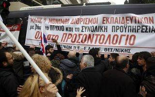 Teachers and other protesters push police buses during clashes near the Prime Minister's office in Athens, Friday, Jan. 11, 2019. About 1,500 people took part in the protest. Teachers' unions oppose the government's selection process for the planned hiring of 15,000 new teachers over the next three years. The banner reads ''Mass Full Time Hiring for Teachers.'' (AP Photo/Thanassis Stavrakis)