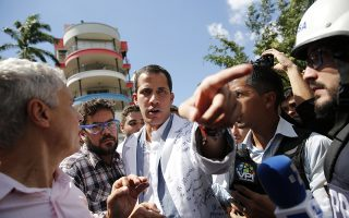 Opposition National Assembly President Juan Guaido, who declared himself interim president of Venezuela, speaks to reporters during a walk out against President Nicolas Maduro, in Caracas, Venezuela, Wednesday, Jan. 30, 2019. Venezuelans are exiting their homes and workplaces in a walkout organized by the opposition to demand that Maduro leave power. (AP Photo/Ariana Cubillos)