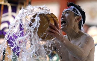 epaselect epa07320202 A participant splashes himself with ice-cold water for a purification ceremony as part of the Daikoku Festival at Kanda Myojin Shrine in Tokyo, Japan, 26 January 2019. Around 40 people participated in the annual new year ice bath ceremony that is thought to purify the soul and sharpen the minds.  EPA/FRANCK ROBICHON
